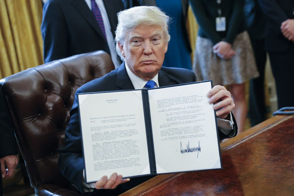 President Donald Trump displays one of five executive orders related to the oil pipeline industry in the Oval Office of the White House in Washington, D.C., U.S., Tuesday, Jan. 24, 2017. (Shawn Thew/Pool via Bloomberg)