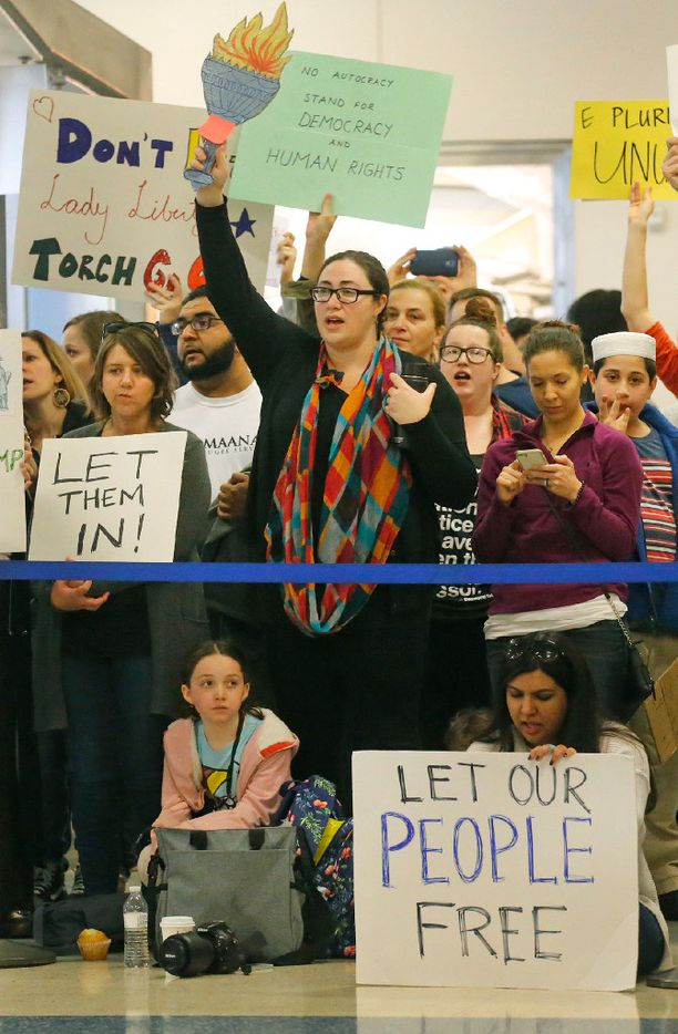 Protesters chant as they hold handmade signs at the international arrivals gate in Terminal D at DFW Airport on Sunday, January 29, 2017.