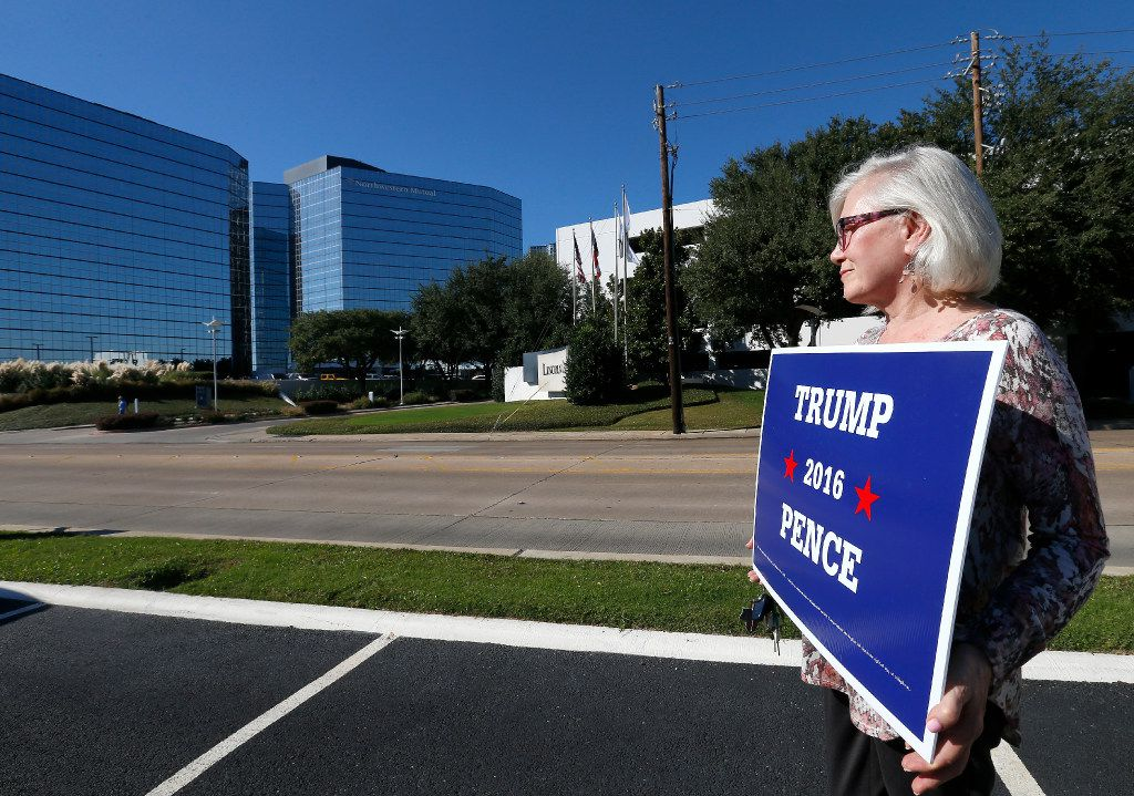 Trump supporter Honey Lanham Dodge (right) stands with a sign near the Hilton Dallas Lincoln Hotel where a fundraising event for Trump is held in Dallas, Tuesday, Oct. 11, 2016.