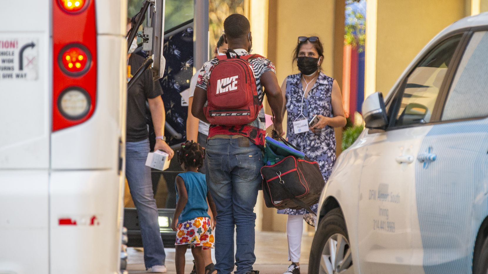 Volunteers with Faith Forward Dallas help migrant families from Haiti and Cuba exit a coach bus at a hotel in Irving, Wednesday, August 11, 2021.