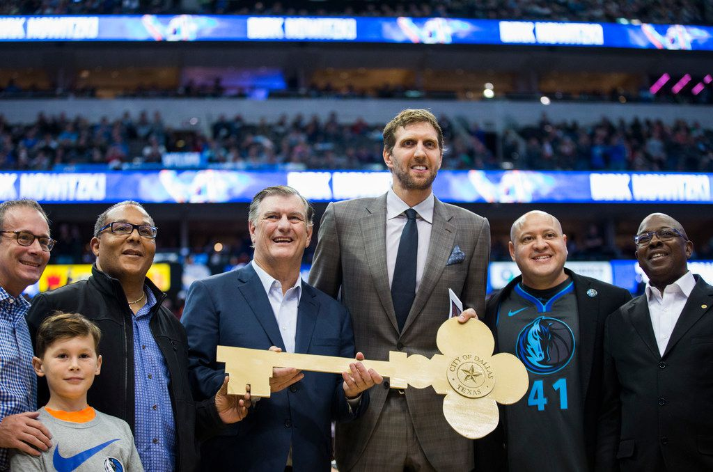 Mayor Mike Rawlings and members of Dallas City Council -- including, in the Mavs jersey, Mayor Pro Tem Adam Medrano -- posed for a photo with Dallas Mavericks forward Dirk Nowitzki after he was presented with the key to the city of Dallas on Nov. 21, 2018 at the American Airlines Center.