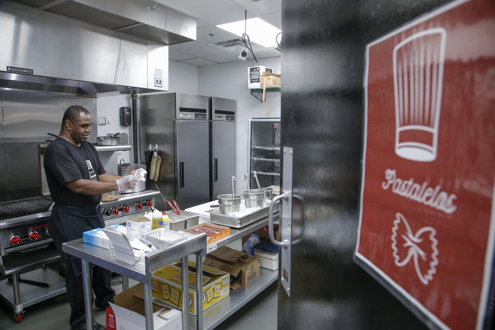 Roger Sackey, owner of Pastalelos, puts on a pair of plastic gloves to prepare a serving of Tomato and Cream Rigatoni at his rented kitchen space at Revolving Kitchen in Garland, Friday, April 30, 2021. Sackey, who has worked in food service for 25 years in New York, started his own business this year.