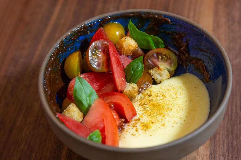 The dish called tomatoes and plums is dressed with fluffy aerated olive oil and a swipe of tomato-skin paste.