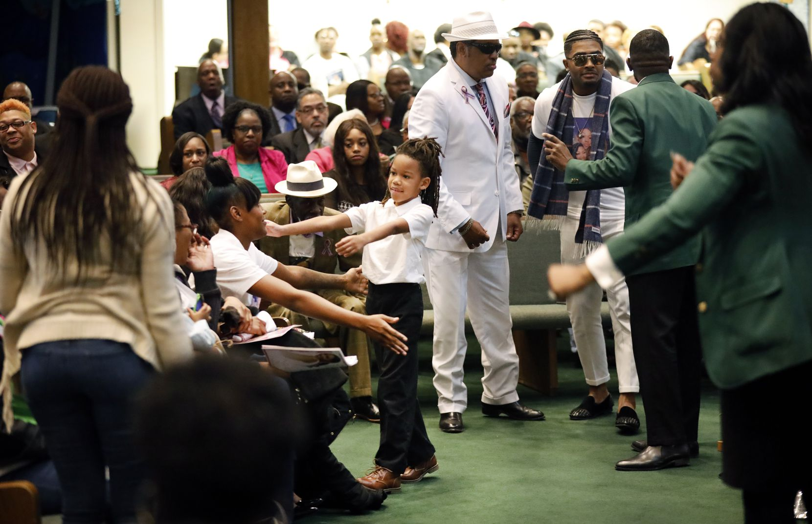 LaTiffiney Rodgers' 7 year-old son, Jorden, reaches for a cousin at a funeral service for his mother in DeSoto on Feb. 22. Police say Rodgers was killed by the father of her children, Johnnie Palmore.