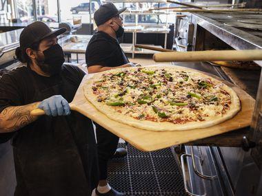 Juan Delgado, a la izquierda, carga una pizza vegetariana en el horno mientras trabaja junto al pizzero Nick Flores, a la derecha, en el rediseñado Serious Pizza en Deep Ellum.  El restaurante de Dallas reabrió el 26 de febrero de 2021 con un nuevo propietario.
