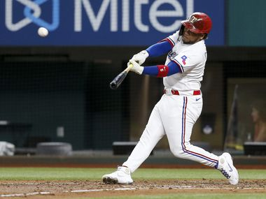 Texas Rangers left fielder Willie Calhoun (5) hits the ball during the third inning against the Oakland Athletics at Globe Life Field on Tuesday, June 22, 2021, in Arlington.