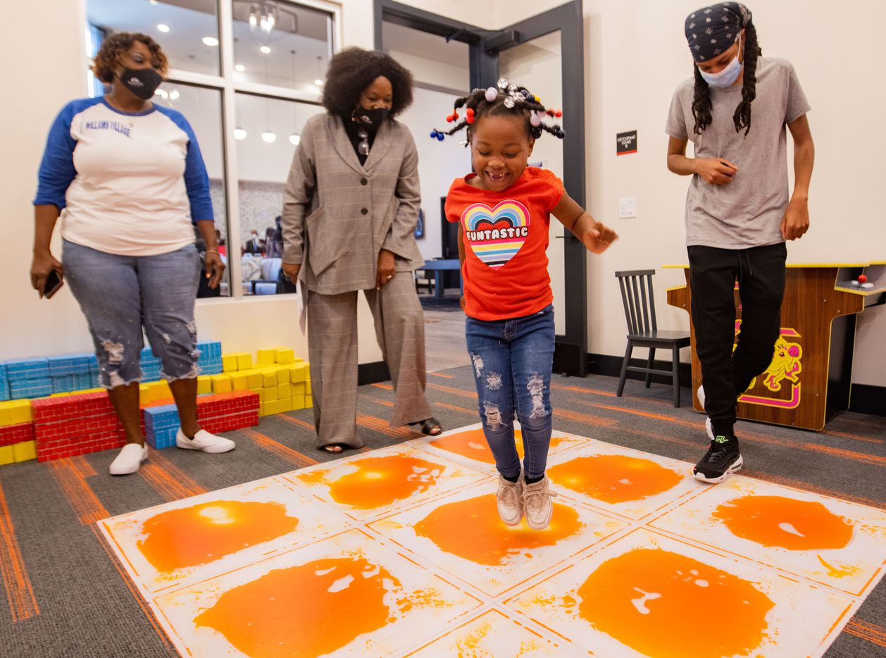 Jazmine Williams, 5, jumps in the playroom while Palladium regional manager April West (center left) gives a tour of the Palladium RedBird apartments.