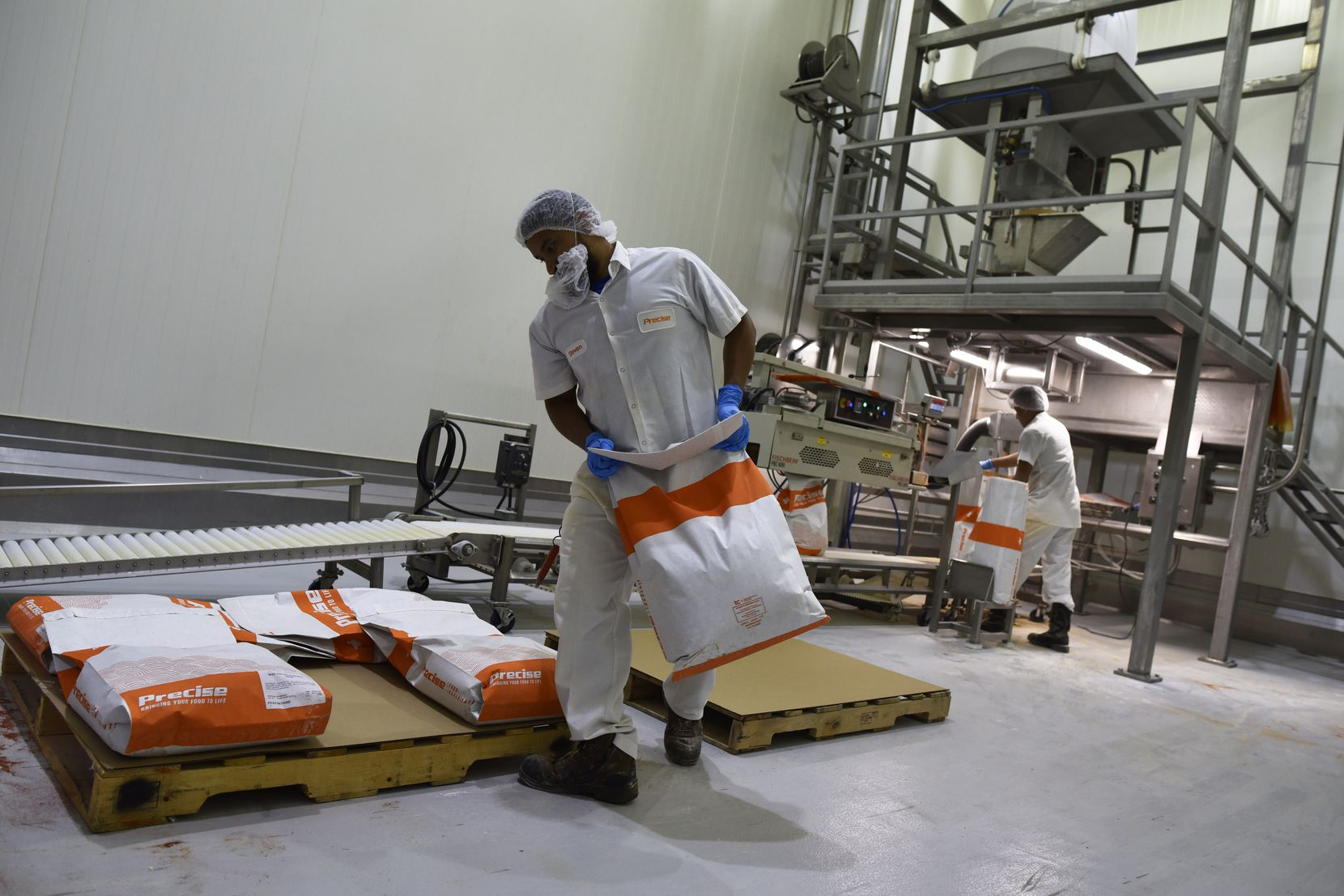 Packaging operators Steven Gallego (left) and Xavier Meza packed beef topping seasoning at a warehouse for Precise Food Ingredients in Carrollton in 2019.