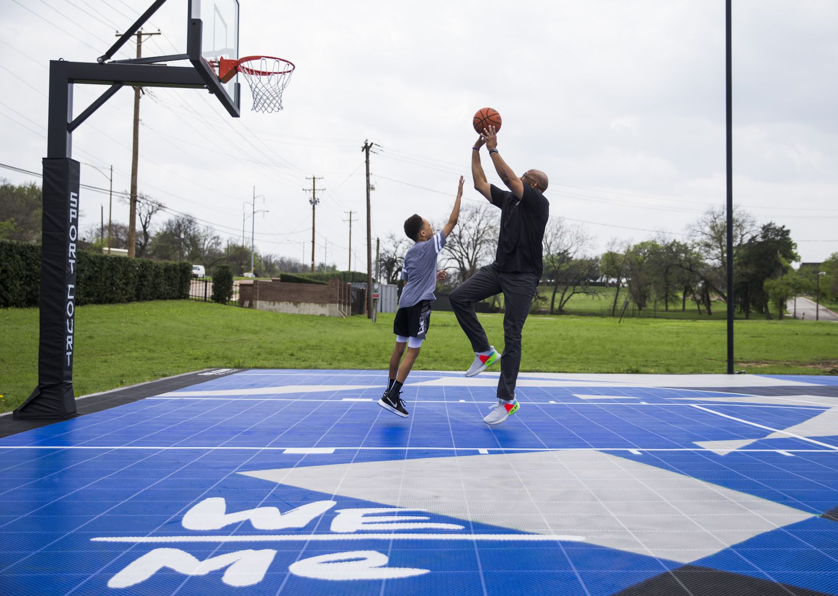 Paul Quinn College president Michael Sorrell played basketball with his 9-year-old son, Michael, last week on the college's campus.