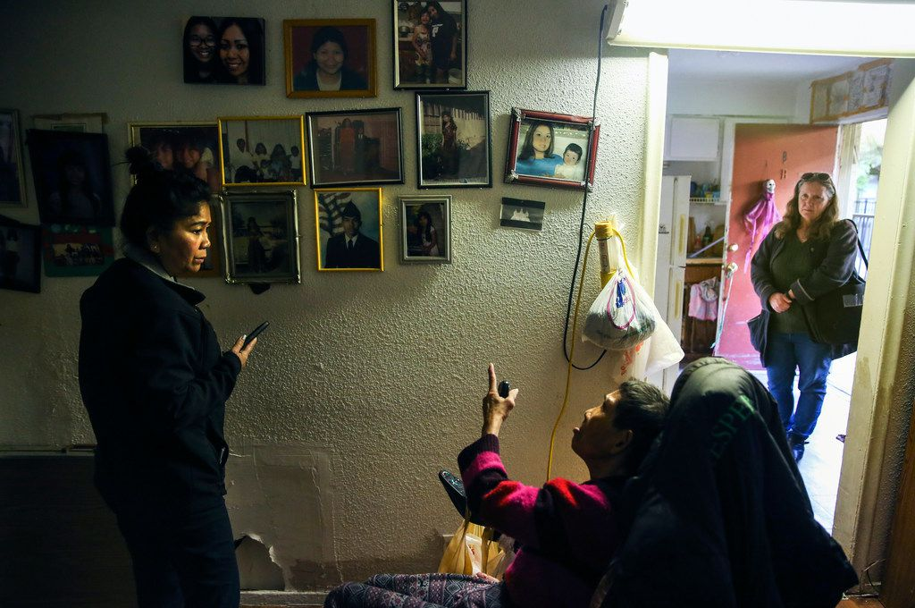 Kimberly Nam (left), a Khmer translator from the Dallas Police Department, translates for Soun Yath, a resident at Bryan Song Apartments, during a visit by Sandy Rollins (right) of the Texas Tenants' Union on Jan. 17, 2019. The apartment complex's residents received a 60-day notice to be out of the property, which is slated for redevelopment this spring.