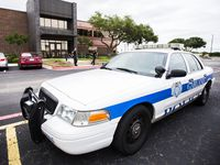 A Garland police car is seen in front of the Garland ISD administration building.