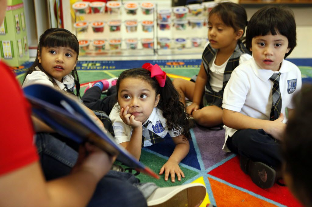 """Pre-k students (L-R) Vida Sanchez, Leah Pina, Isabella Jaramillo and Carlos Escobedo, all three-years of age, sit on a carpet while listening to their teacher read a Spanish childrens book titled """"Un Beso en Mi Mano,"""" during a class activity at Leonides Gonzalez Cigarroa MD Elementary School. Ben Torres/Special Contributor 09052015xPUB"""