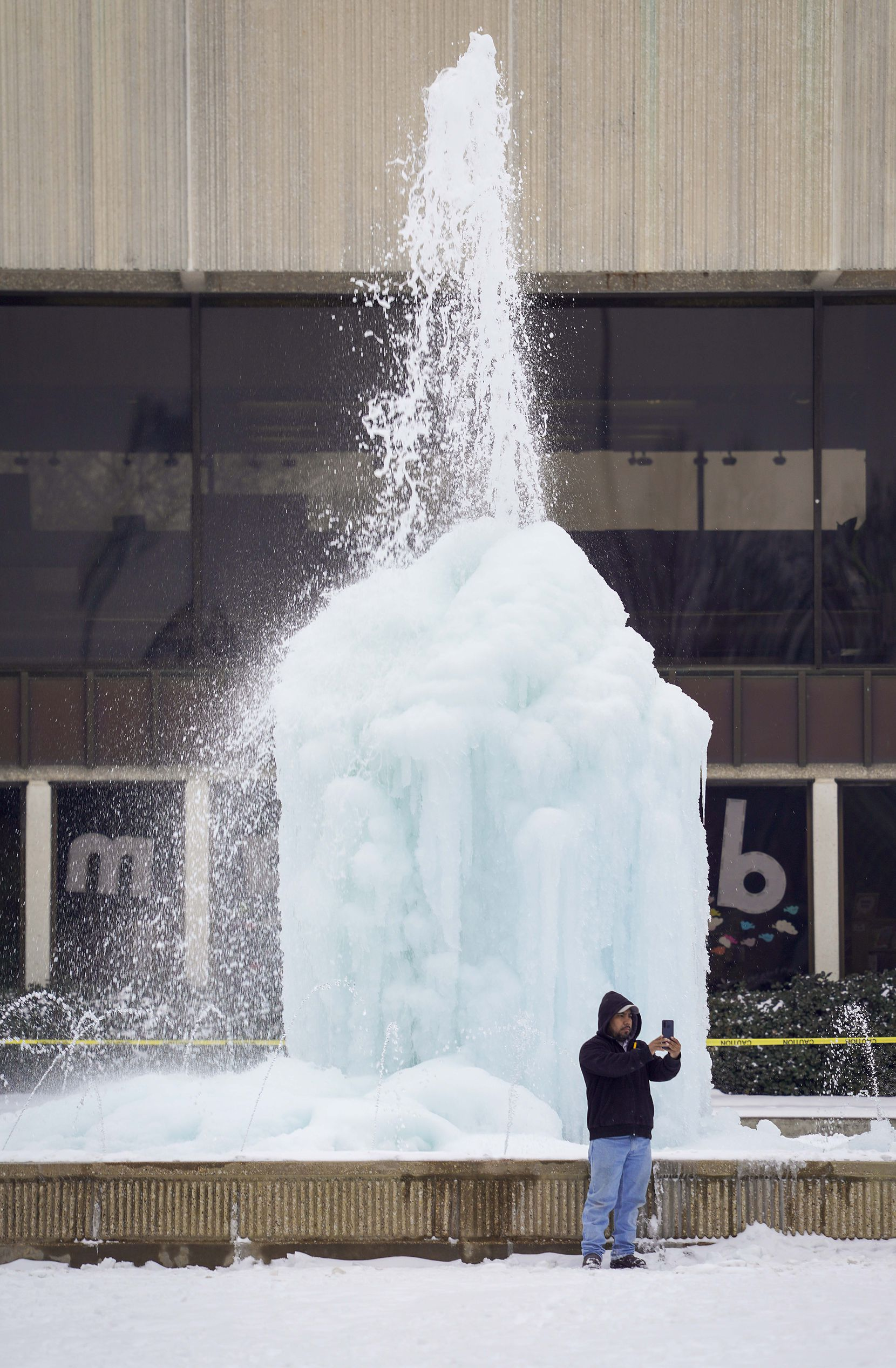 Carlos de Jesus takes a selfie in front of the frozen fountain at the Richardson Civic Center after a second winter storm brought more snow and continued freezing temperatures to North Texas on Wednesday, Feb. 17, 2021, in Richardson. After watching the fountain freeze of the the past few days, de Jesus, who lives nearby, said he decided to take a photo Wednesday on his way home from work.