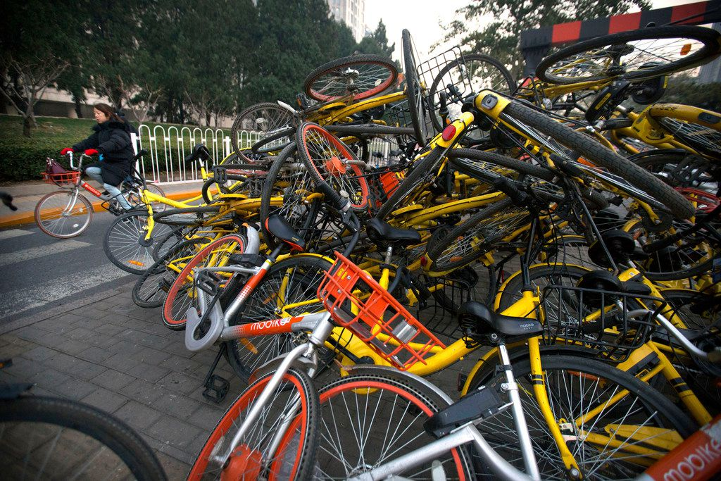 A woman rides a bicycle past Mobike and Ofo branded  bicycles piled on a traffic median in Beijing on Nov. 21. Chinese government officials have introduced regulations in recent months to help tame China's booming bicycle-sharing industry that has flooded the streets of its major cities with bicycles for hire.