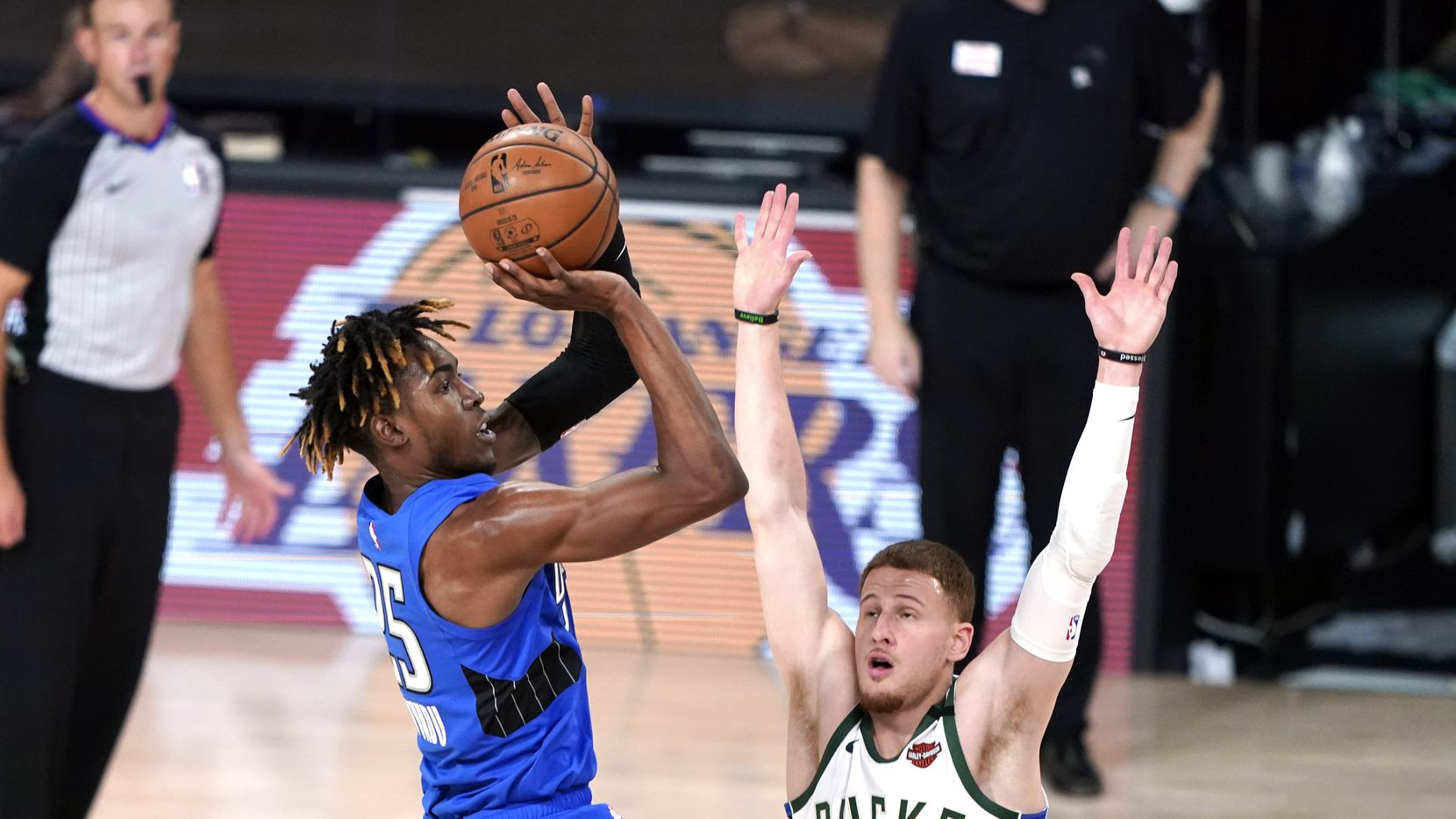 Orlando Magic's Wes Iwundu (25) shoots as Milwaukee Bucks' Donte DiVincenzo (0) defends during the second half of an NBA basketball first round playoff game Saturday, Aug. 29, 2020, in Lake Buena Vista, Fla. (AP Photo/Ashley Landis)
