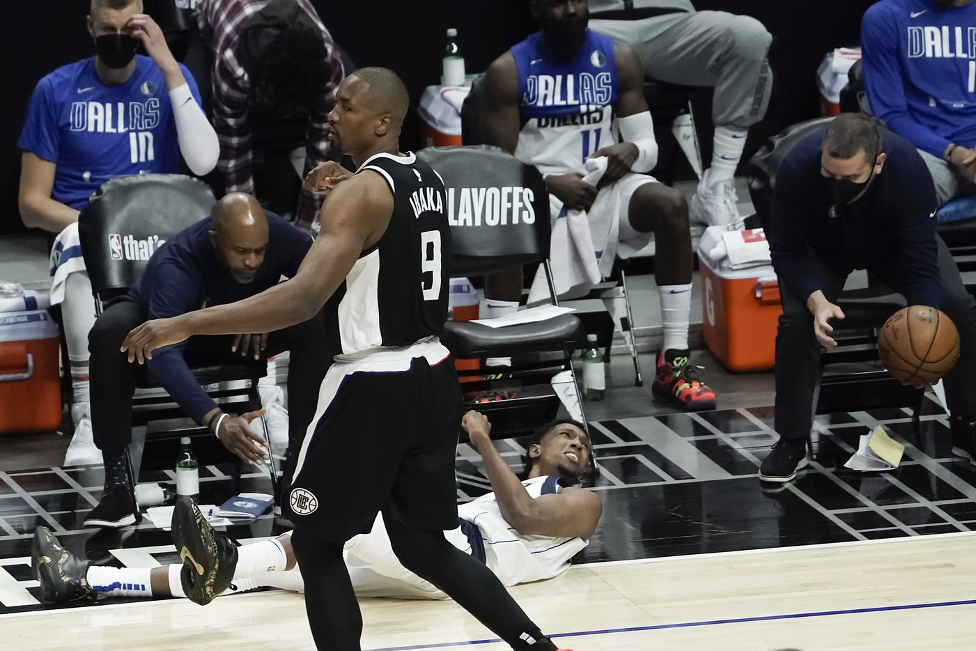 Dallas Mavericks guard Josh Richardson (0) tumbles chasing a loose ball against LA Clippers center Serge Ibaka (9) during the second half of an NBA playoff basketball game at Staples Center on Saturday, May 22, 2021, in Los Angeles.