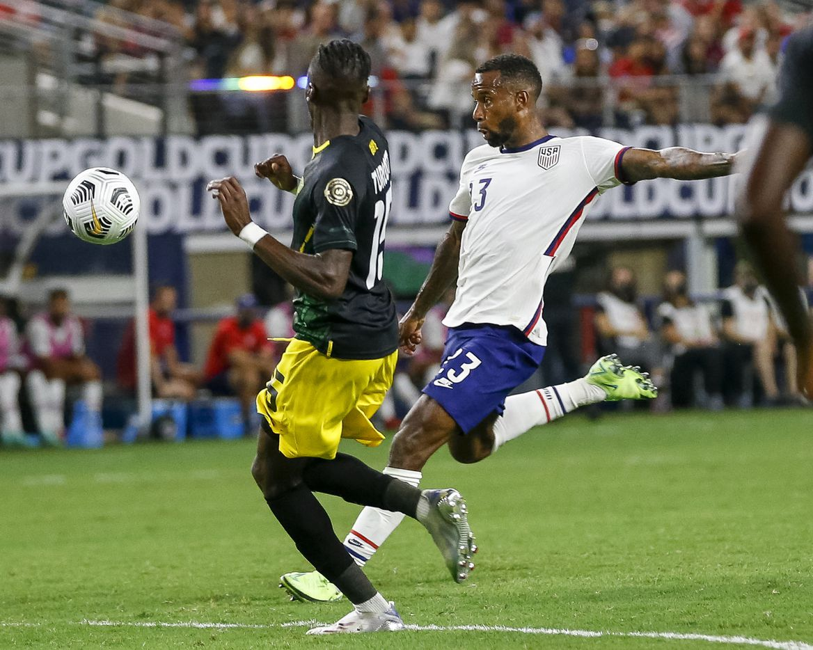 USA midfielder Kellen Acosta (13) shoots the ball around Jamaica forward Blair Turgott (15) during the first half of a CONCACAF Gold Cup quarterfinal soccer match at AT&T Stadium on Sunday, July 25, 2021, in Arlington. (Elias Valverde II/The Dallas Morning News)