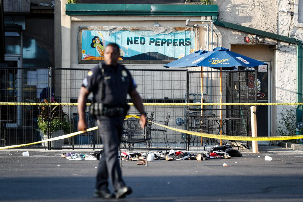 Shoes are piled outside the scene of a mass shooting including Ned Peppers bar, Sunday, Aug. 4, 2019, in Dayton, Ohio. Several people in Ohio have been killed in the second mass shooting in the U.S. in less than 24 hours, and the suspected shooter is also deceased, police said.