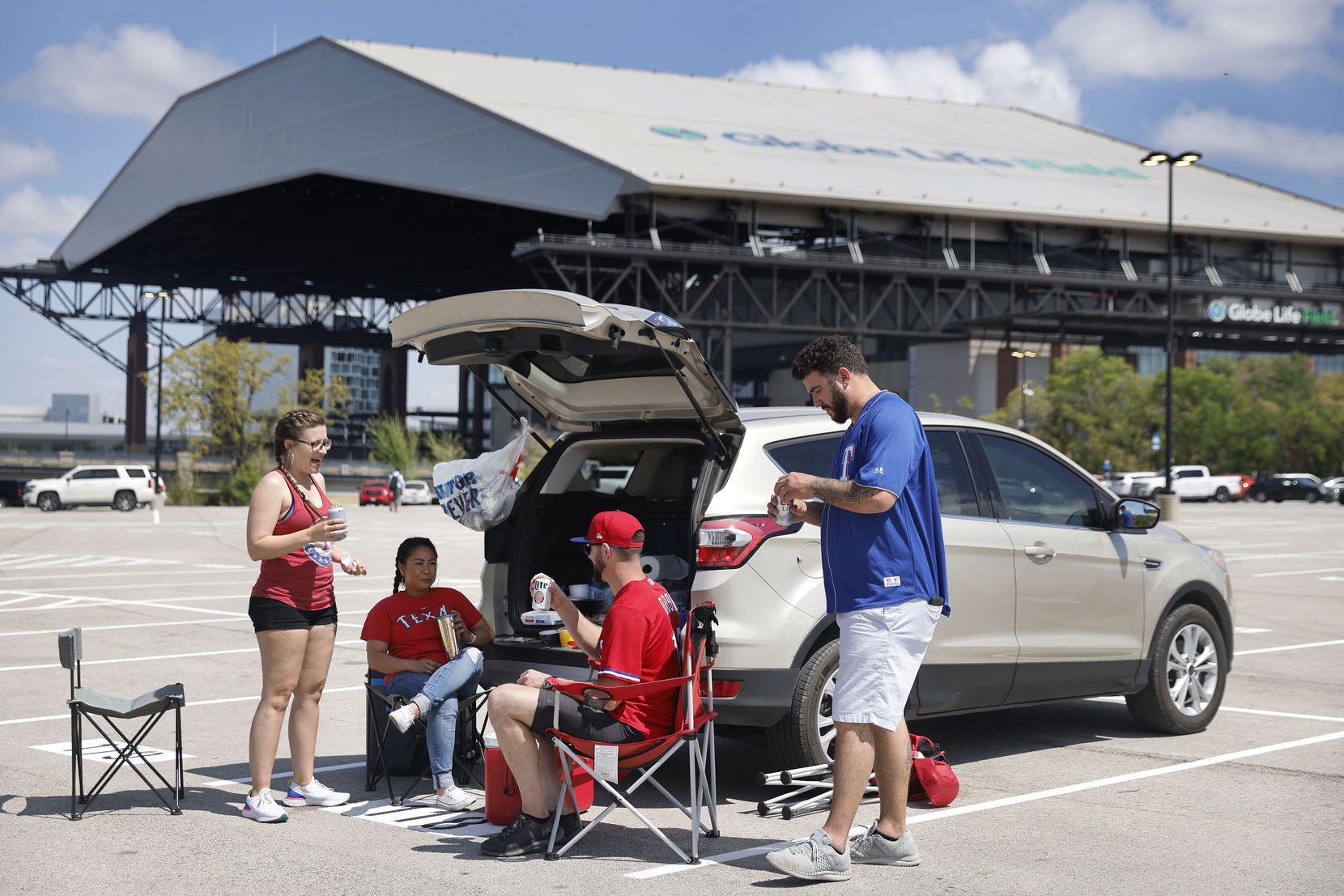 Texas Rangers fans enjoy an Opening Day tailgate party on private property outside of Globe Life Field in Arlington, Monday, April 5, 2021. The Rangers are facing the Toronto Blue Jays in the home opener. (Tom Fox/The Dallas Morning News)