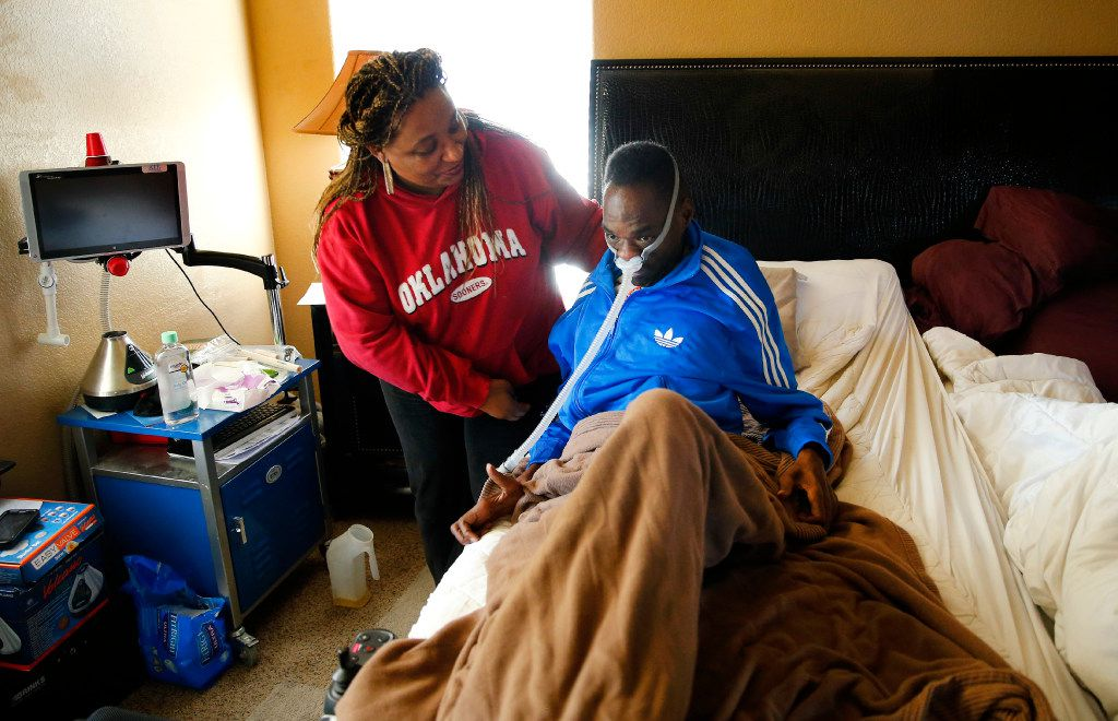 Lorraine Dixon helps her husband as he rests in bed. (Tom Fox/The Dallas Morning News)