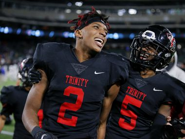Euless Trinity junior running back Ollie Gordon (2) and junior defensive back Jayveus Lyons (5) celebrate a 49-45 win over Allen after a high school Class 6A Division I Region I semifinal football game at Globe Life Park in Arlington, Saturday, December 26, 2020. Trinity won 49-45.