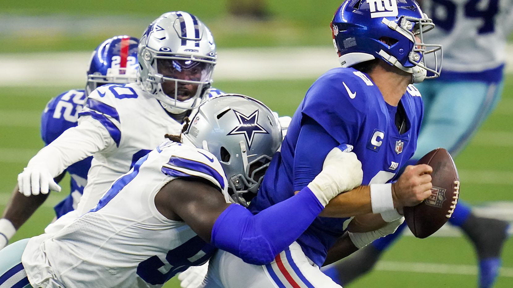 Giants quarterback Daniel Jones (8) fumbles as he's hit by Cowboys defensive end DeMarcus Lawrence (90) during the second quarter of a game at AT&T Stadium on Sunday, Oct. 11, 2020, in Arlington.
