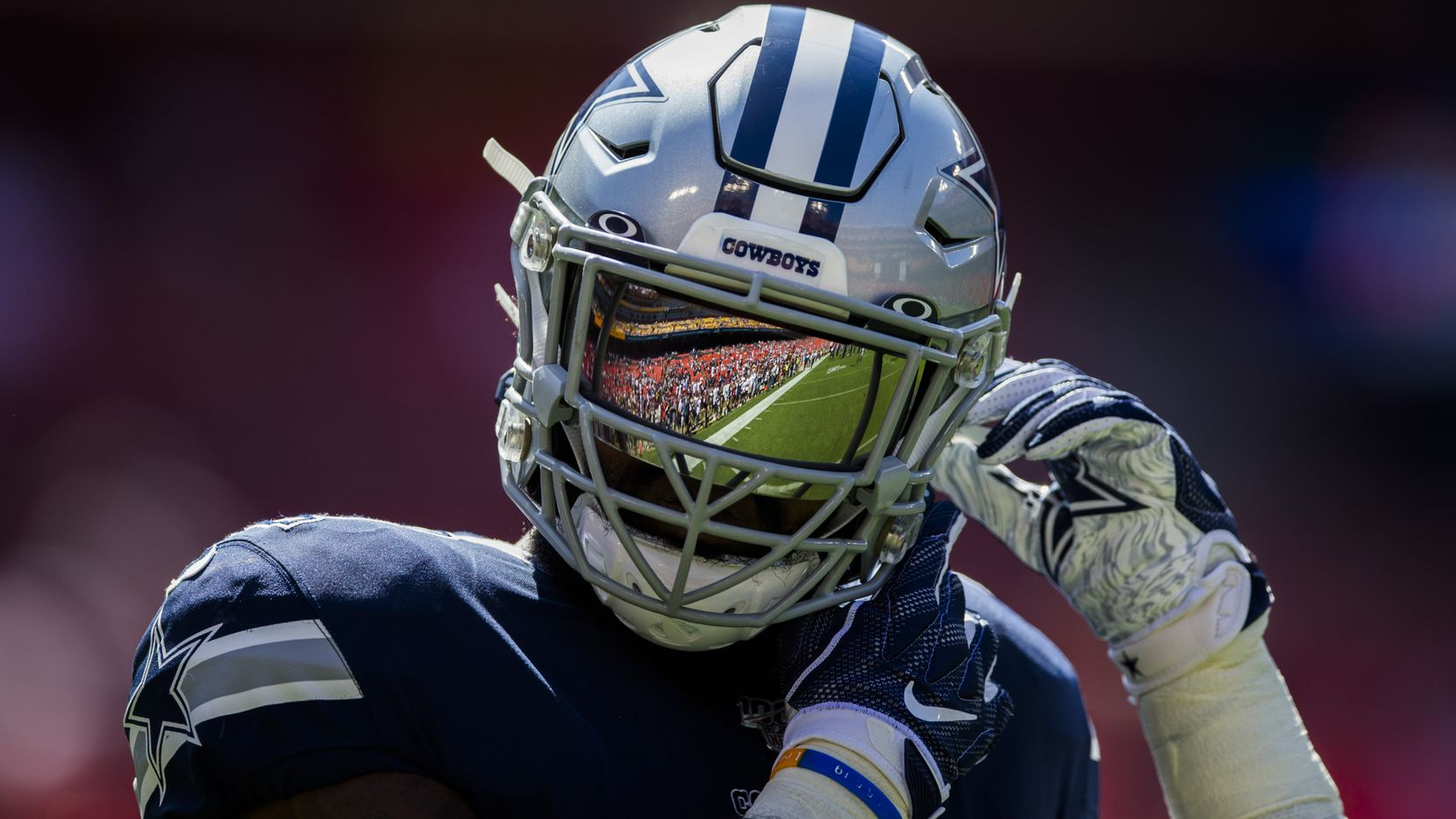 Dallas Cowboys running back Ezekiel Elliott (21) has the field reflected in his helmet as he warms up before an NFL game between the Dallas Cowboys and the Washington Redskins on Sunday, September 15, 2019 at FedExField in Landover, Maryland.