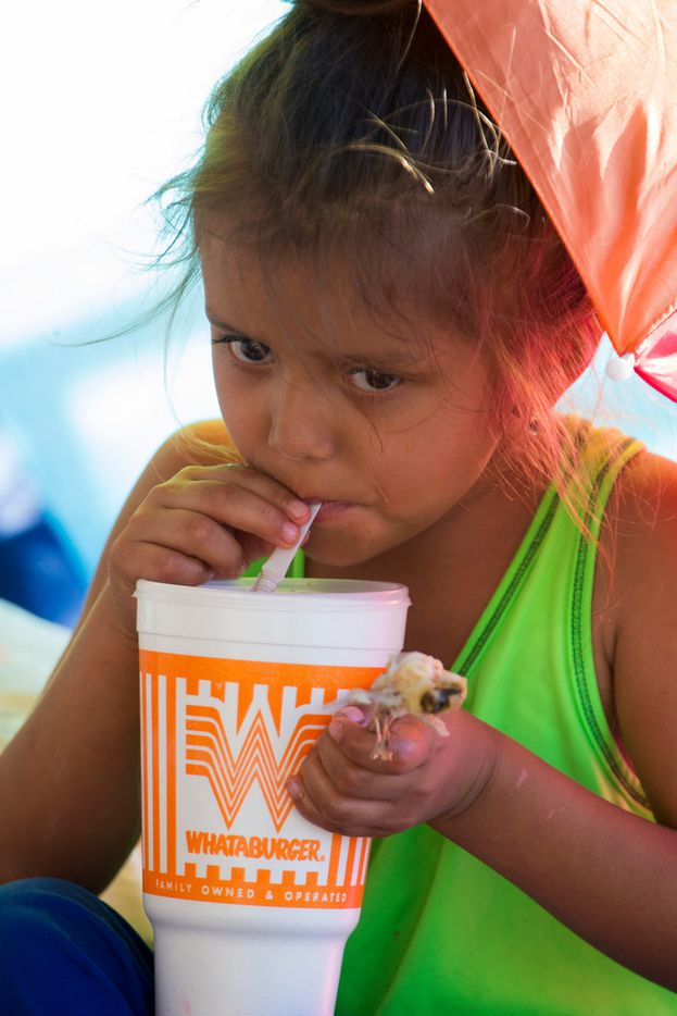 Michelle, 6, drinks from a Whataburger cup on the U.S. side of the Hidalgo bridge in between Hidalgo, Texas, and Reynosa, Mexico, on June 9, 2018.