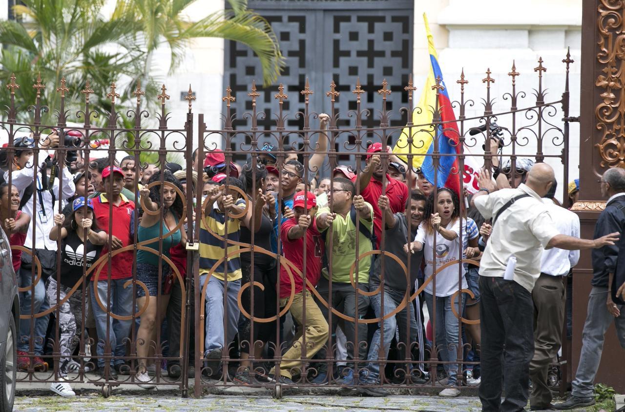 Simpatizantes del presidente Nicolás Maduro derriban la puerta de entrada al patio de la Asamblea Nacional en Caracas, el domingo. (AP)(AP)