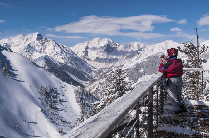 A skier captures the view of Pyramid Peak and the Maroon Bells from the deck of the ski patrol cabin atop Loge Peak in Aspen Highlands.