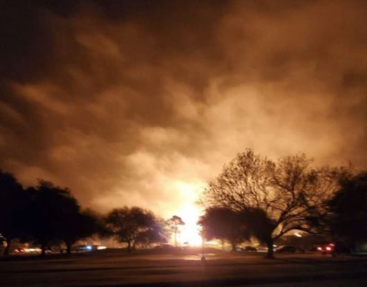 Flames are visible as the sky glows orange where a chemical plant exploded in Port Neches on Wednesday morning.