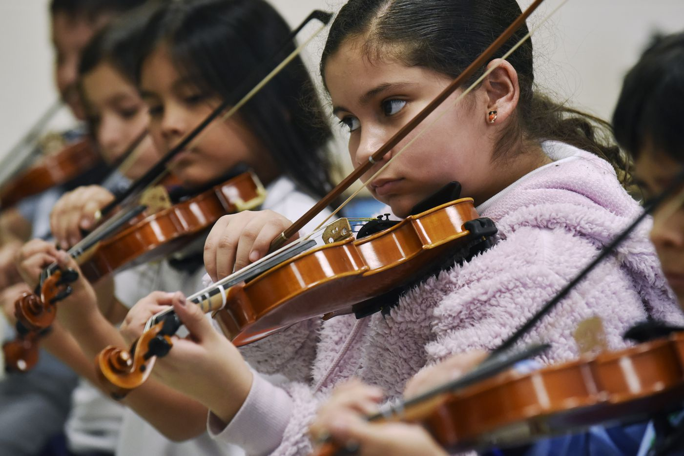 "Bella Lupian, right, plays her violin with a group of fourth graders during an afterschool violin class at Zaragoza Elementary School. Bella told us that among her favorite things about the class is ""what a wonderful teacher Ms. Nicole is."""