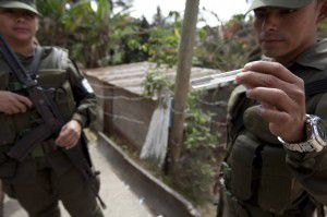 Guatemalan soldiers  on Friday show a mosquito larva found during a fumigation campaign against the Aedes aegypti mosquito in the La Comuna 2 neighborhood of Guatemala City.  (AP Photo/Moises Castillo)
