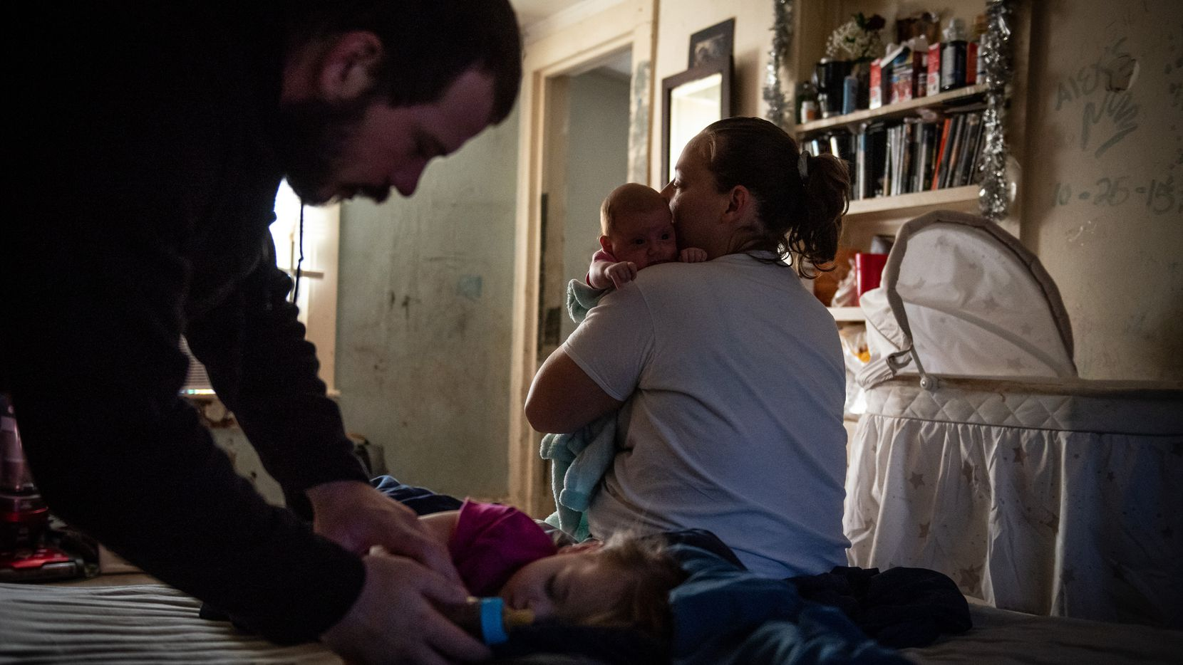 Tiffany Revilla holds her newborn baby, Cheyenne, as her partner, David Romine, cares for their 1-year-old daughter, Adillie, at their home in Fort Worth on Dec. 1.