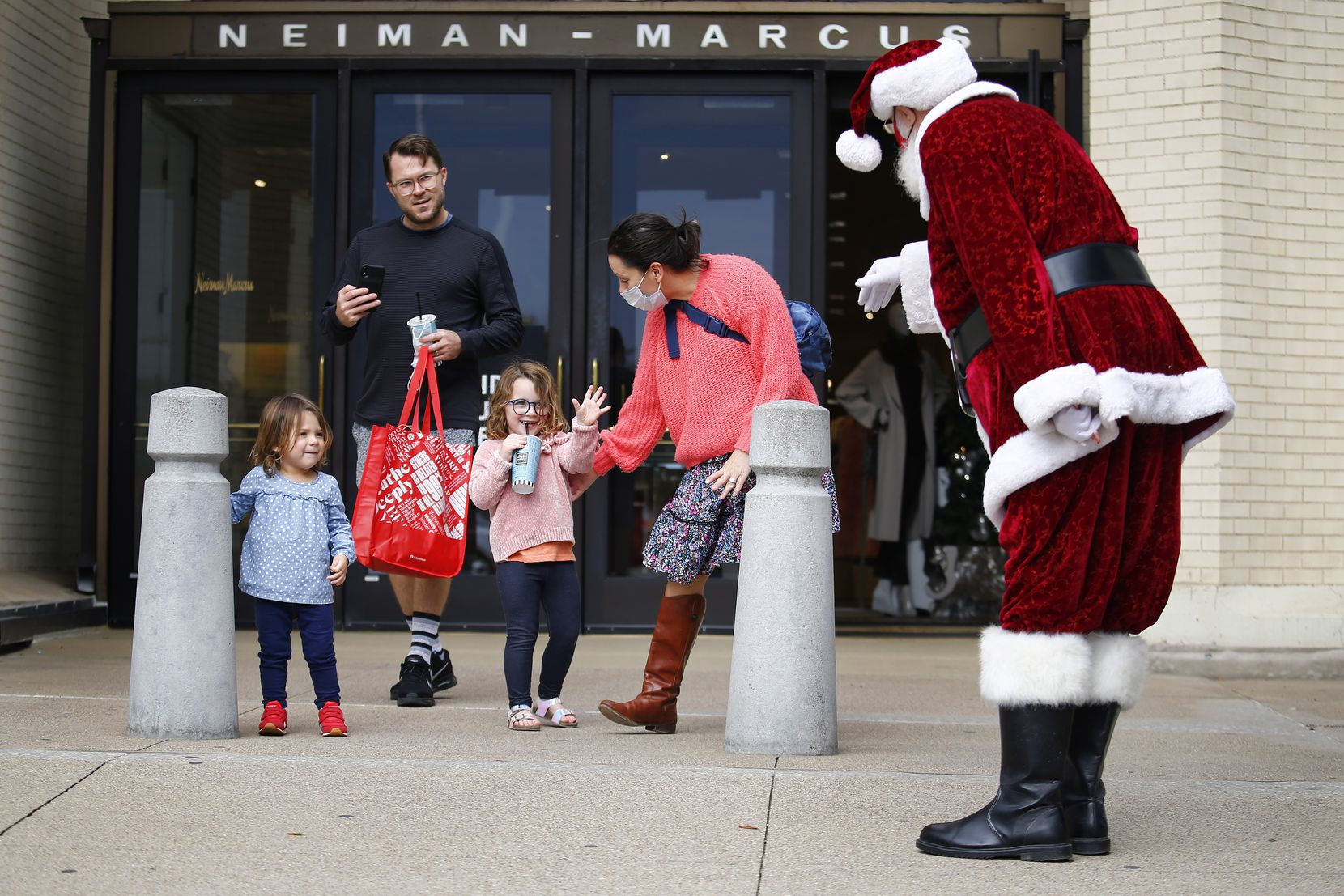 Stella Helt, 4, waves to Santa Claus, aka Mike Davis, as she and her sister, Evie, dad Bob and mom Gayle leave the Neiman Marcus store at NorthPark Center in Dallas. Santa was helping with curbside pickup at the store.