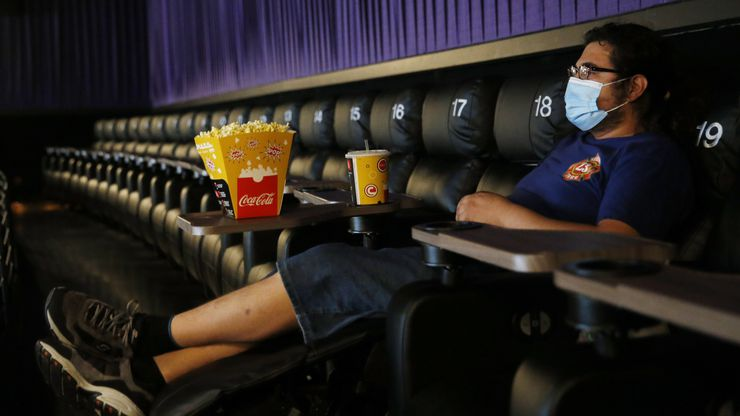 """Ben Levy of Plano watches trailers play as he waits for """"Sonic the Hedgehog,"""" to start at Cinemark West in Plano, on Friday, June 19, 2020. After being closed for months due to the coronavirus pandemic, the theater reopened today."""