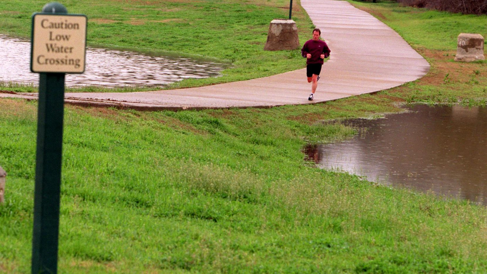 An unidentified jogger exercises along Campion Trail in north Irving. Flooding along the trail has led Irving to close several areas.