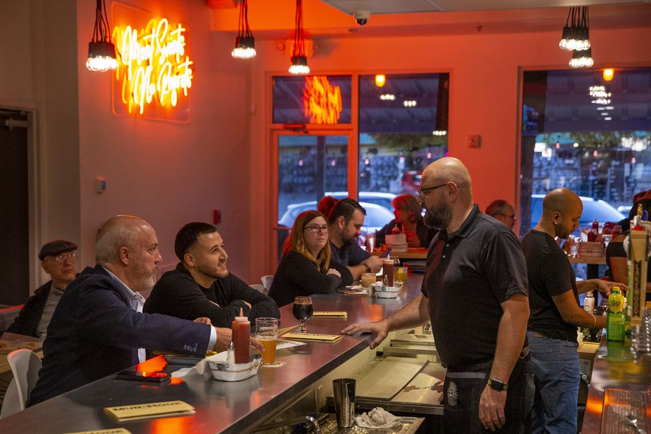 Owner Bryan Kaeser (right) visits with customers during the soft opening of Mudhook in Duncanville.