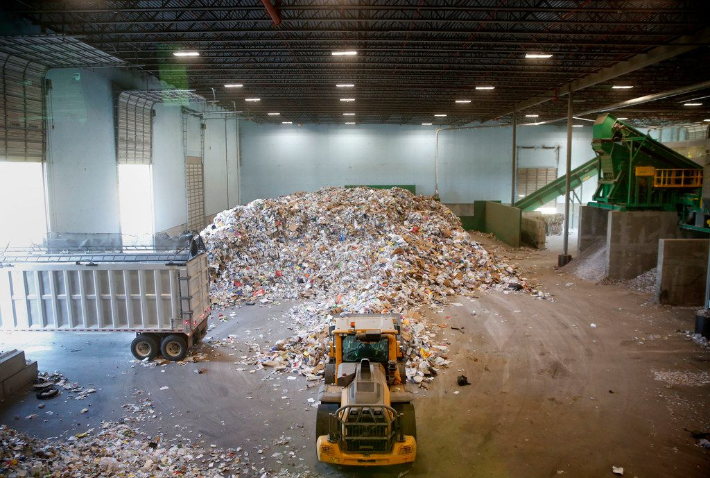 Recyclable material is piled on the tipping floor ready to be sorted at the Dallas recycling facility.