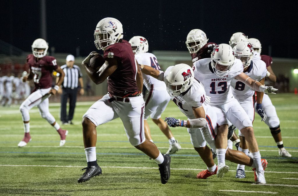 Lewisville sophomore running back Damien Martinez (6) breaks through McKinney Boyd senior defensive backs Plae Wyatt (41) and Jake Fex (13) in the first half of a high school football game on Friday, September 13, 2019 at Max Goldsmith Stadium in Lewisville.