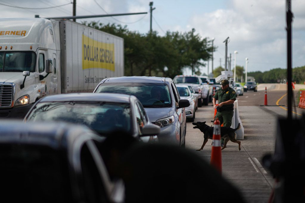 A U.S. Border Patrol Agent with a K-9 checks incoming cars at the checkpoint in Falfurrias, north from the border toward San Antonio, Texas, June 27.