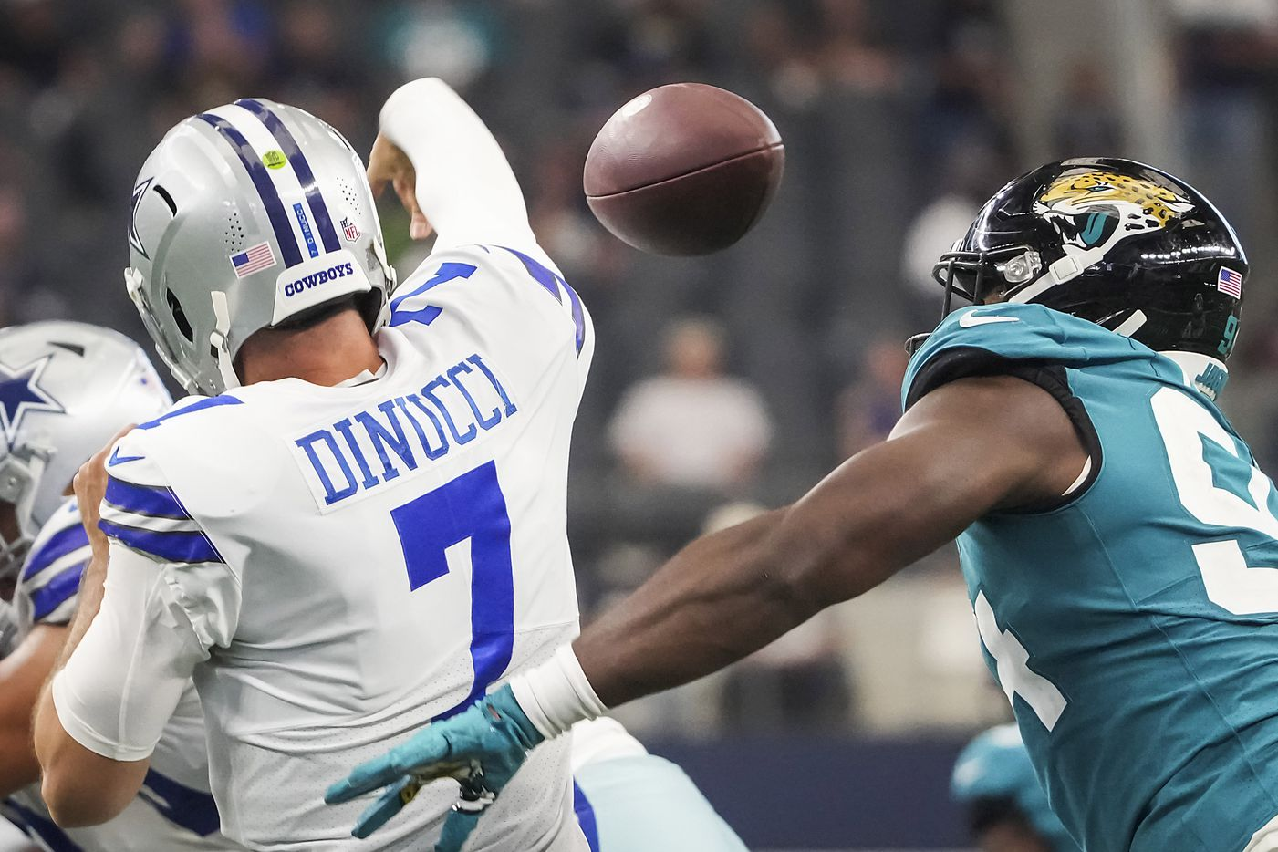 Dallas Cowboys quarterback Ben DiNucci (7) fumbles as he is hit by Jacksonville Jaguars defensive end Aaron Patrick (94) during the second half of a preseason NFL football game at AT&T Stadium on Sunday, Aug. 29, 2021, in Arlington. (Smiley N. Pool/The Dallas Morning News)