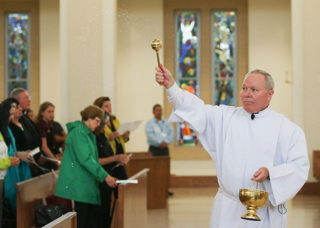 Bishop Edward J. Burns bless parishioners with holy water during a Ceremony of Sorrow on Tuesday, Oct. 9, 2018 at St. Cecilia Catholic Church in Dallas. Following the service, the first of four town halls was held to address the current crisis of sexual abuse by clergy, including allegations of sexual abuse by the former pastor of St. Cecilia Catholic Church, Reverend Edmundo Paredes. (Ryan Michalesko/The Dallas Morning News)