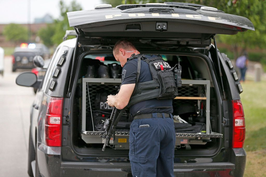 An Irving police officer gets tactical gear on as he arrives at the shooting scene.