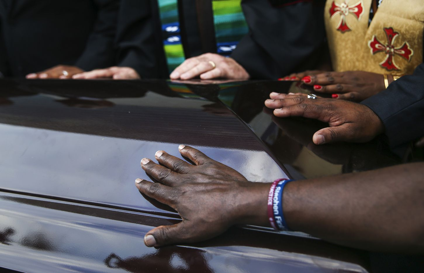 Members of the clergy and community place their hands upon two empty coffins during the protest.