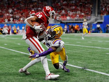 ATLANTA, GEORGIA - DECEMBER 28: Wide receiver Charleston Rambo #14 of the Oklahoma Sooners is tackled by cornerback Woodi Washington #5 of the Oklahoma Sooners during the Chick-fil-A Peach Bowl at Mercedes-Benz Stadium on December 28, 2019 in Atlanta, Georgia. (Photo by Kevin C. Cox/Getty Images)