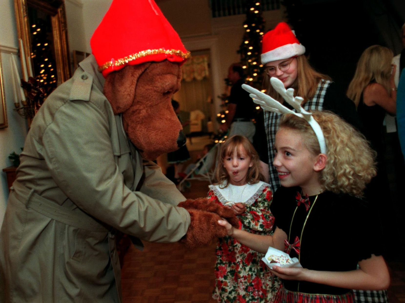 McGruff the Crime Dog, left, greets Scarlett Deering, then 9, right, while her sisters Savannah, 5, and Joanna Deering, 14, look on at the 91st birthday celebration of Winnetka Heights community at historic J. P. Blake House in Oak Cliff.