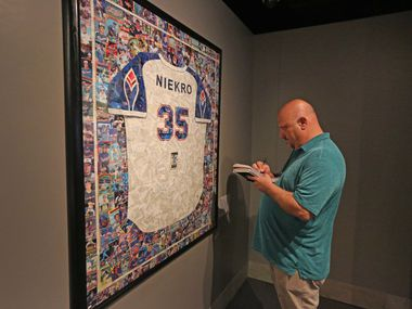 The Dallas  Morning News baseball writer Evan Grant examines a mosaic of baseball cards in the shape of a Phil Niekro jersey at the Baseball Hall of Fame in Cooperstown, NY, photographed on Tuesday, May 30, 2017.