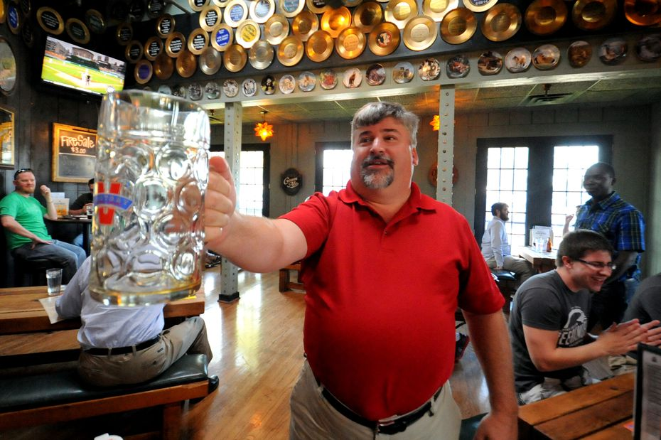 Behind Flying Saucer Addison regular Richard Nash are the gold 'Ring of Honor' plates given to customers who drink 200 different beers at the bar.