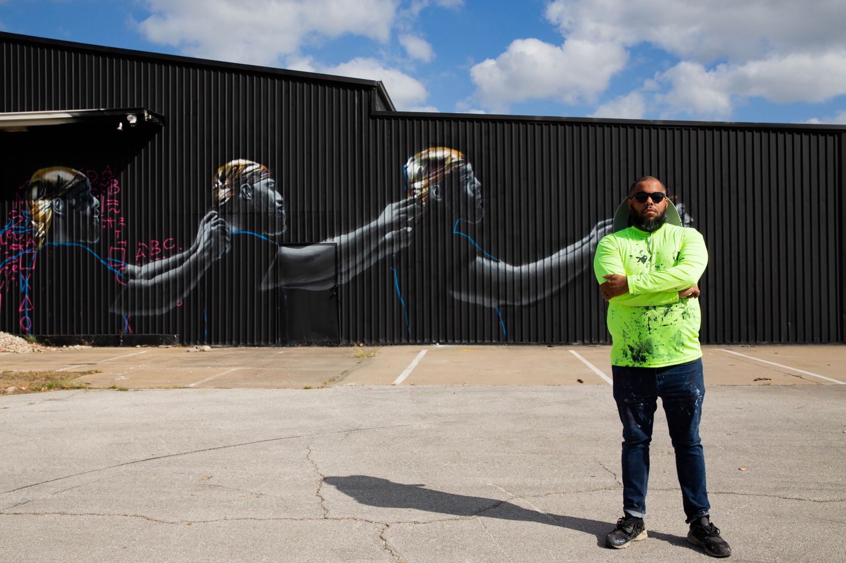 Jeremy Biggers poses in front of his mural as part of The Wild West Mural Fest in Dallas on Tuesday, Oct. 22, 2020. Biggers mural depicts how Black men can hold each other responsible while achieving their potential.
